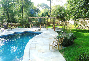 Circular bluestone pool deck integrates irregular pool shape into new site design