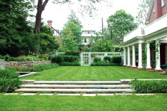 View across formal lawn flanked by fountain and gardens