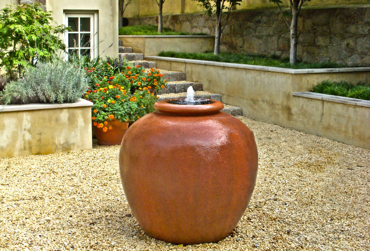 A rich orange vessel fountain is located in bed of pea gravel