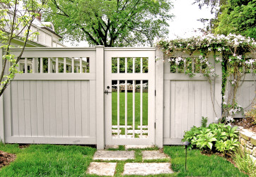 A white wooden fence provides privacy and extends the home's architectural style into the garden