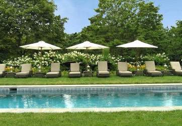 View across pool to chaise lounges and umbrellas with garden background