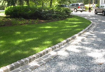 An entry drive is lined with stone cobbles to ensure a clean line between the lawn and gravel