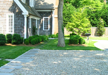 A stone path seamlessly integrates the gravel drive and lawn creating a modern aesthetic