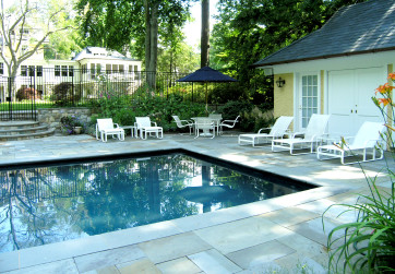 An existing pool is enhanced by a new pool house and deck framed with gardens and stone retaining walls