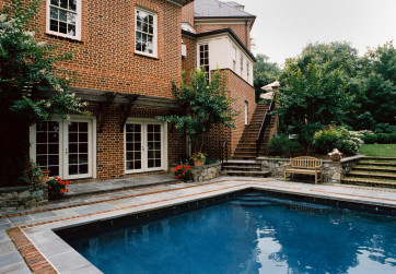 The stone and brick deck nestle the pool into the site