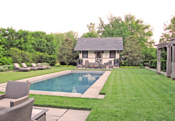 Wide stone coping surrounds a serene pool located in a lush lawn panel