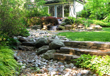 A dry riverbed is not only a gorgeous feature in this back garden but also an effective strategy to manage stormwater
