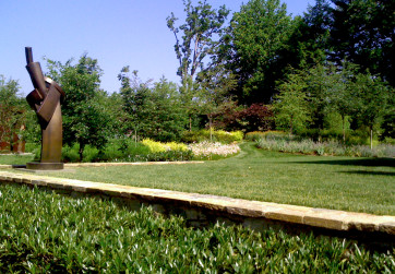 Stone retaining wall creating lawn and meadow path
